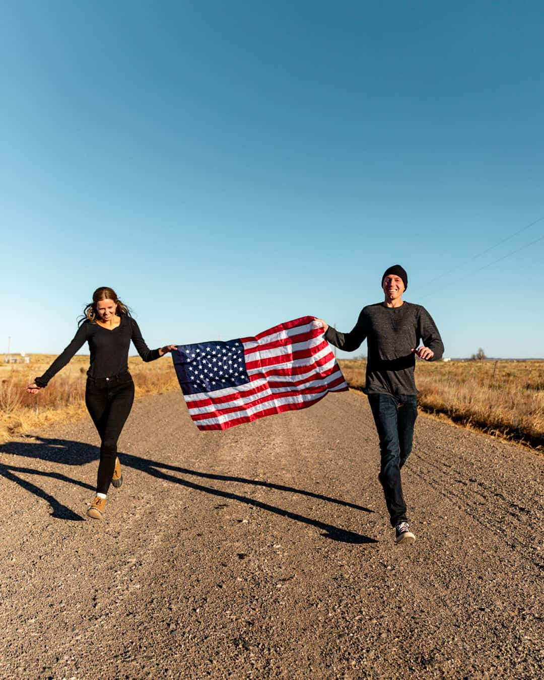 The Passport Couple running with American Flag