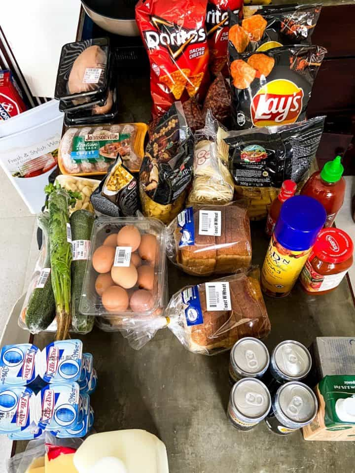 Counter covered in groceries - chips, eggs, meat, veggies