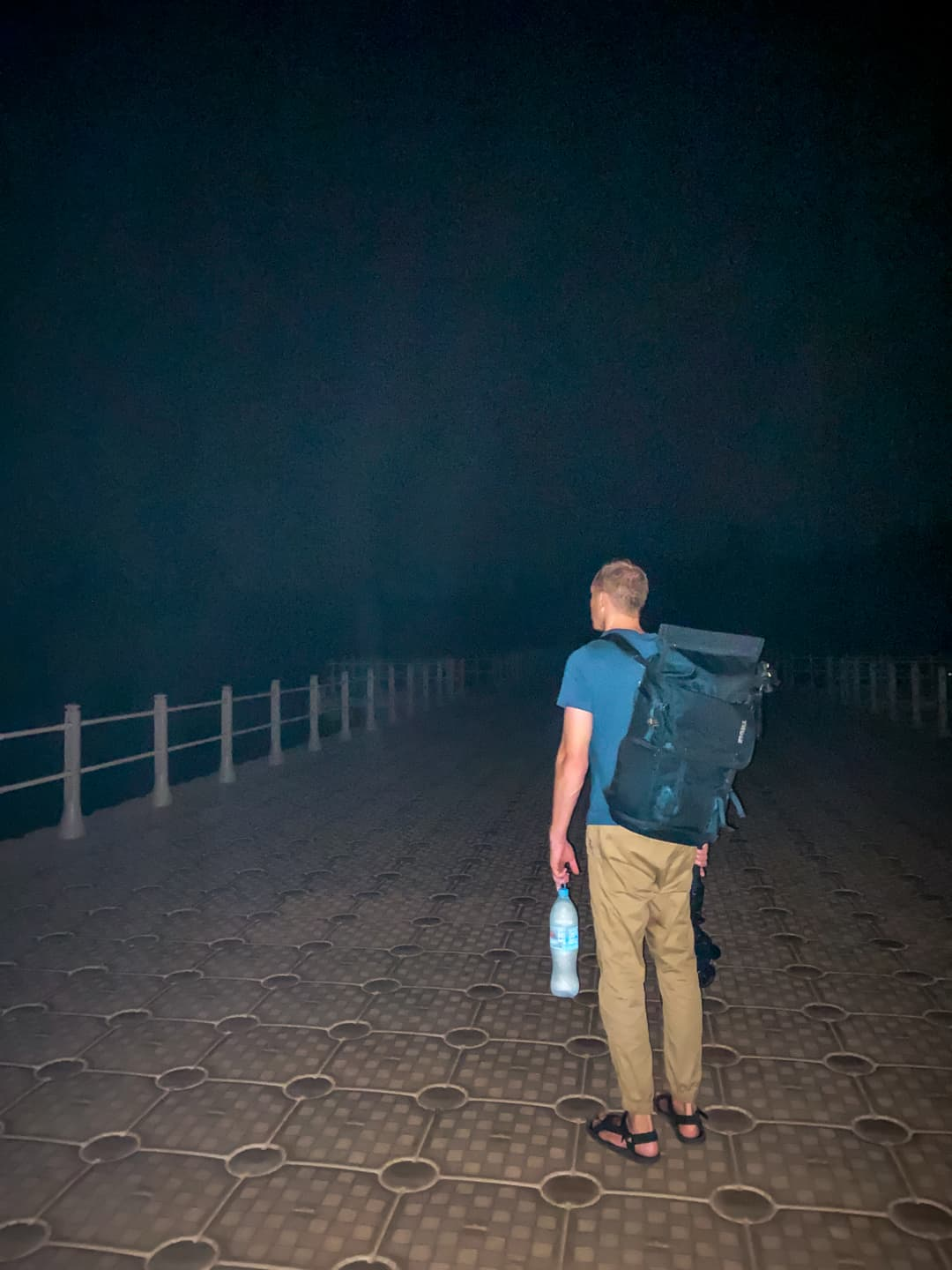 Nate standing on floating bridge in complete darkness