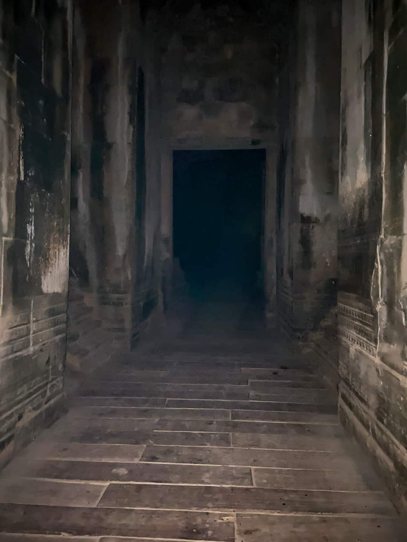 Dark hallway of Angkor Wat lit up by camera flash