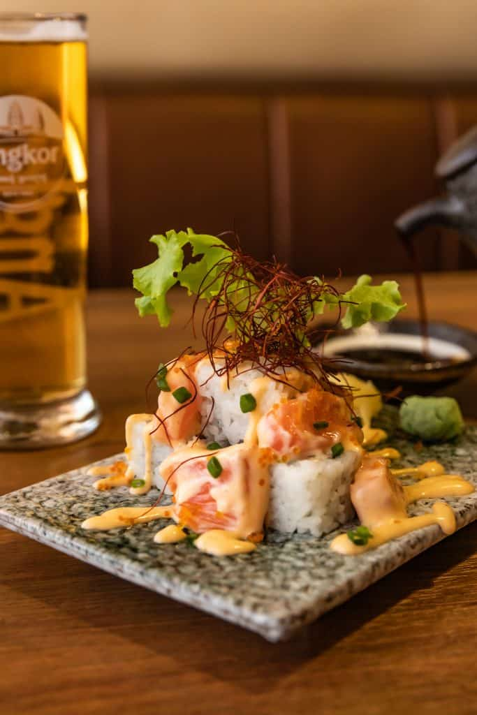 Sushi and beer with soy sauce in background