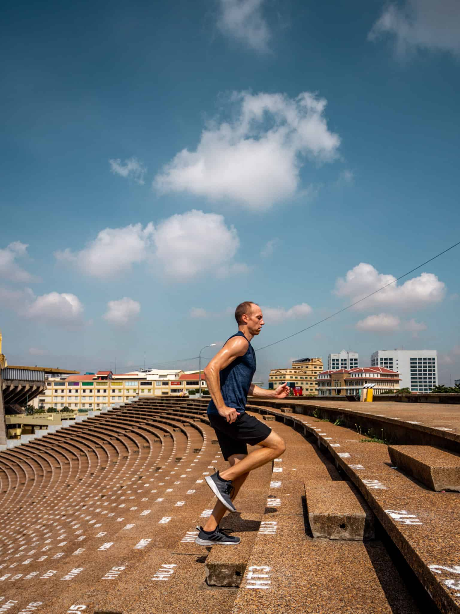 Nate running up stairs at National Olympic Stadium in Phnom Penh
